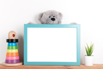 Interior poster mock up for nurcery, children's room with vertical wooden frame, toys and teddy bear on white wall background