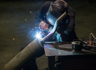 welder in mask welds metal
