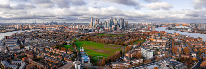 London, England - Aerial Panoramic skyline view of Bank and Canary Wharf, central London's leading financial districts with famous skyscrapers at golden hour sunset during cloudy skies.