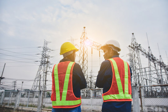 Man and Women Engineering standing communication at power plant  electrical system background