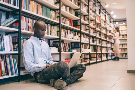 Ethnic man browsing laptop in library
