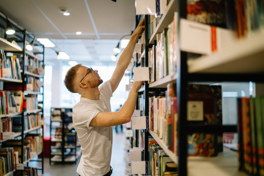 Focused guy reaching for book on top shelf