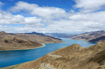 Beneath a plethora of puffy, white clouds, Lake Yamdrok glows turquoise between the desert mounatains of the Tibetan Plateau in Brahmaputra Valley of the Tibet Autonomous Region, China.