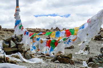 Lung ta prayer flags, white scarves (khatas) and cairns flank the border of a Chinese military zone in Gampa Pass in Brahmaputra Valley in Tibet Autonomous Region of China.