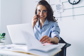 Smiling brown haired woman talking on smartphone in office