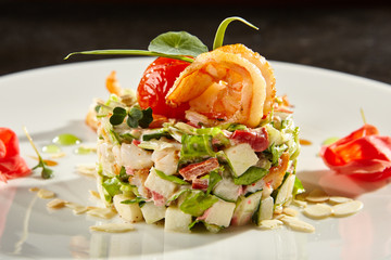 Olivier salad with crab meat and shrimps on white plate