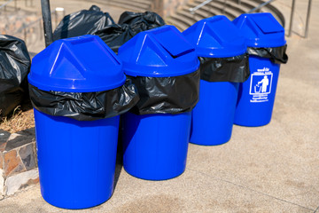 Large blue plastic garbage trash bins for recycling waste standing upright arranged in a row in a city park