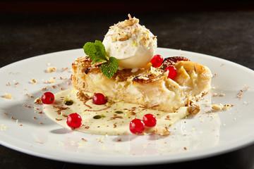 Apple pie slice with ice cream scoop side view