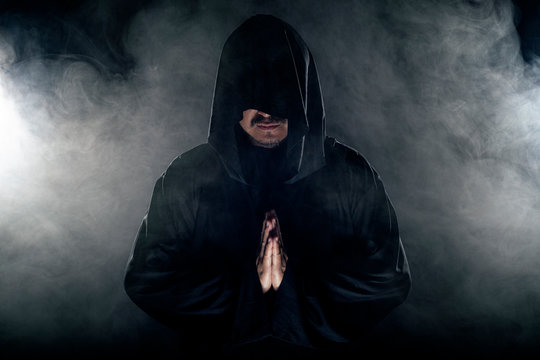 Man dressed in a dark robe looking like a cult leader on a smoky or foggy background.  He looks like a creepy evil villain