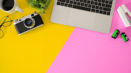 Wall Mural - Top view of modern workplace with laptop computer and office supplies on pink and yellow desk