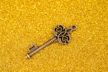 Vintage key on gold glitter background