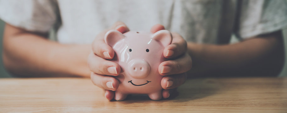 Panoramic image, Man hand holding piggy bank on wood table. Save money and financial investment