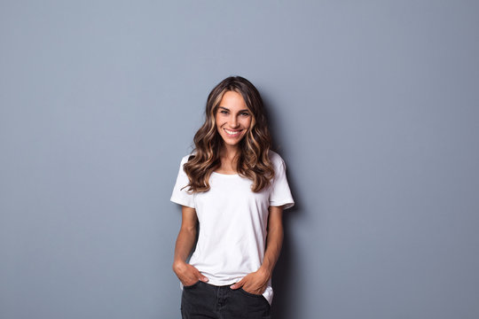 Indoor portrait of beautiful woman wearing white casual T-shirt, looking happily in camera.