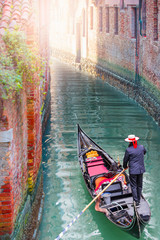 Keuken foto achterwand Gondolas Venetian gondolier punting gondola through green canal waters of Venice Italy