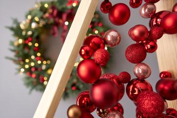 Close up red christmas balls. Alternative wooden christmas tree. A handmade Christmas tree.