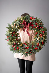 Beautiful festive wreath of fresh spruce in woman hands. Xmas circlet with red and gold ornaments and balls. Christmas mood. Gray wall on background.