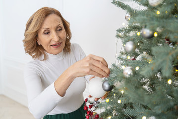 Positive delighted female person decorating Christmas tree