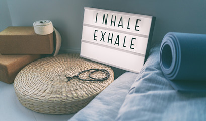 Photo on textile frame Yoga school Yoga breathing INHALE EXHALE sign at fitness class on lightbox inspirational message with exercise mat, mala beads, meditation pillow. Accessories for fit home lifestyle.