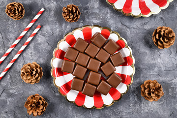 Top view of German traditional sweets called 'Dominosteine', gingerbread, jelly and marzipan layered glazed food sold around Christmas season on red and white striped plate