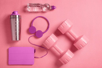 Dumbbells, headphones and protein shaker on the fitness mat