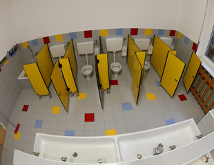 long sink and toilet of a nursery with yellow doors without chil