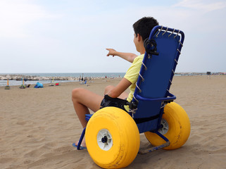 young disabled boy in a special wheelchair with big inflatable w