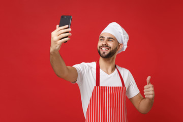 Smiling young chef cook or baker man in striped apron toque chefs hat isolated on red wall background. Cooking food concept. Mock up copy space. Doing selfie shot on mobile phone, showing thumb up.
