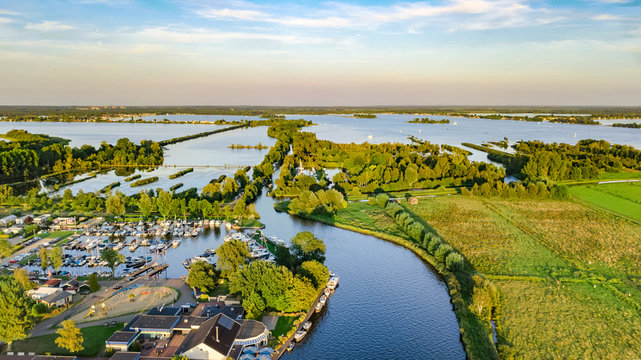 Aerial drone view of typical Dutch landscape with canals, polder water, green fields and farm houses from above, Holland, Netherlands