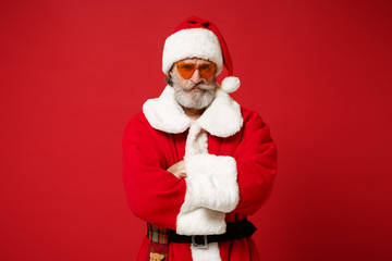 Serious Elderly gray-haired mustache bearded Santa man in Christmas hat, sunglasses posing isolated...