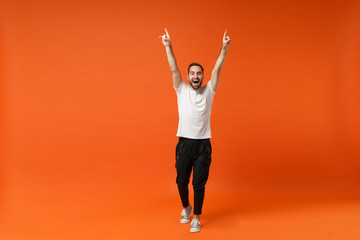 Funny young man in casual white t-shirt posing isolated on orange background, studio portrait. People sincere emotions lifestyle concept. Mock up copy space. Rising hands, pointing index fingers up.