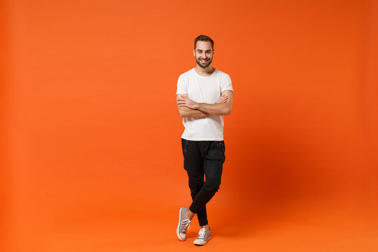 Smiling attractive young man in casual white t-shirt posing isolated on orange wall background studio portrait. People sincere emotions lifestyle concept. Mock up copy space. Holding hands crossed.