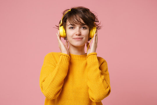 Beautiful young brunette woman girl in yellow sweater posing isolated on pastel pink wall background studio portait. People lifestyle concept. Mock up copy space. Listening music with headphones.