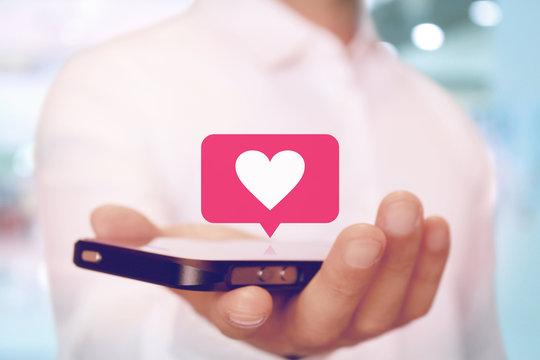 スマートフォンでハートの通知マーク SNS heart on smartphone SNS app