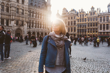 Photo sur cadre textile Bruxelles Woman stands in the square Grand Place in Brussels, Belgium at sunset.