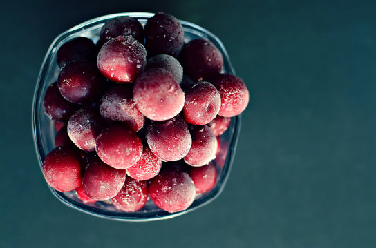 frozen cherry in a glass on a dark background, copy space