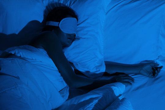 Woman sleeping with a sleep mask on her eyes