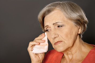 Close up portrait of crying beautiful senior woman isolated on grey background