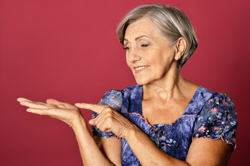 Close up portrait of beautiful senior woman pointing isolated on red background