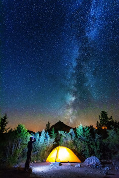 Vertical landscape images with a night starry sky and a milky way against the backdrop of a yellow tourist tent, which is highlighted from the inside.