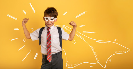 Young boy student acts like a super hero. Yellow background