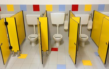 three toilets of a bathroom nursery with yellow doors