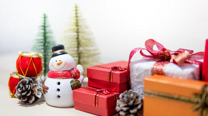 Christmas decoration concept. Smiley snowman toy, gift box, pine cone and mini Christmas tree on the table. Decorative objects for Xmas and New Year holiday. Ornament for Festive season celebration