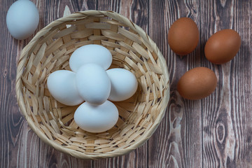several fresh chicken eggs in a straw basket on a wooden background. Healthy eating concept