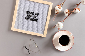 Mug of coffee, cotton branches, letterboard with quote Wake up and be awesome