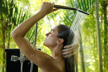 Woman washing under the shower in open air bathroom