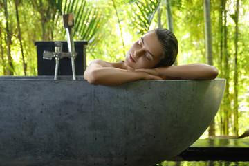 Woman relaxing in bathtub in open air bathroom