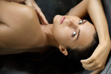 Beautiful woman lying and relaxing in the stone bathtub