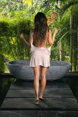 Woman in open air bathroom with stone bath