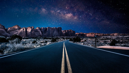 An endless desolate road leading into Arches National Park in Moab, Utah, USA under a dark and starry night sky.