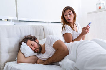 Cheating wife using mobile phone lying in bed next to his sleeping husband. Affair. Cheating Girlfriend Chatting On Phone While Boyfriend Sleeping In Bedroom At Night. Selective Focus.